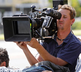 A technician holds a large video camera to his eye