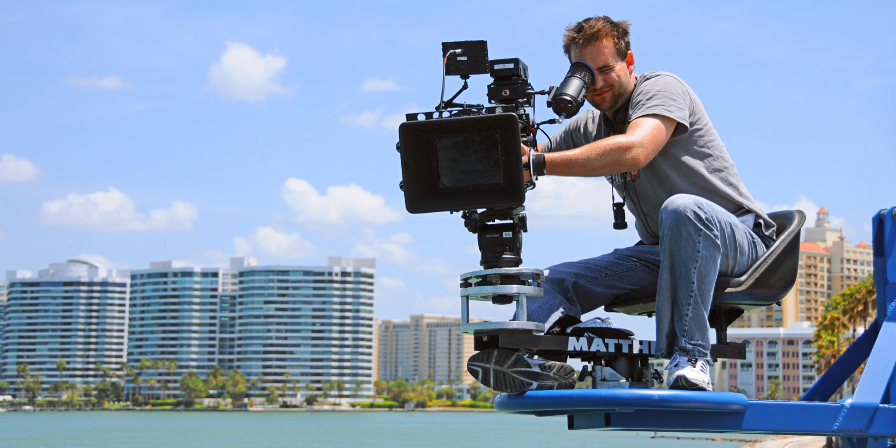 Cameraman filming with a professional rig near the Sarasota waterfront